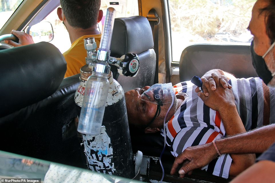 A COVID-19 patient waits in an ambulance outside a hospital in Jaipur as India's healthcare system buckles due to Covid