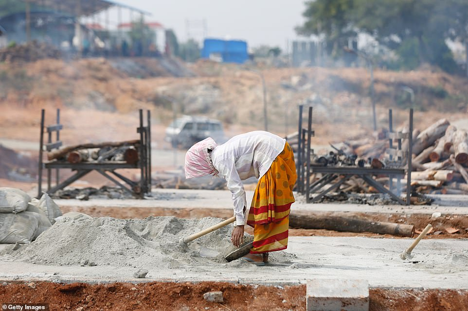 A female cremation worker helps to construct temporary platforms to burn the bodies of Covid victims in Bengaluru, India