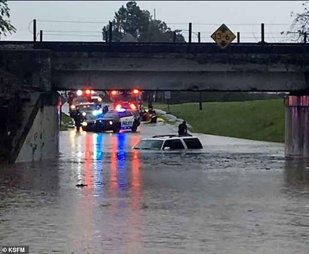 Police assist an Arkansas resident whose vehicle became flooded during a storm on Wednesday