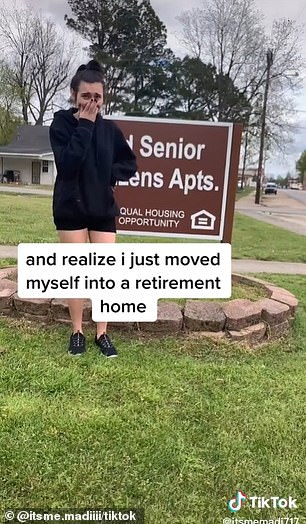 Hilarious mistake: In her now-viral video, she can be seen standing in front of a 'Senior Citizen Apartments' sign at the complex, hanging her head in embarrassment
