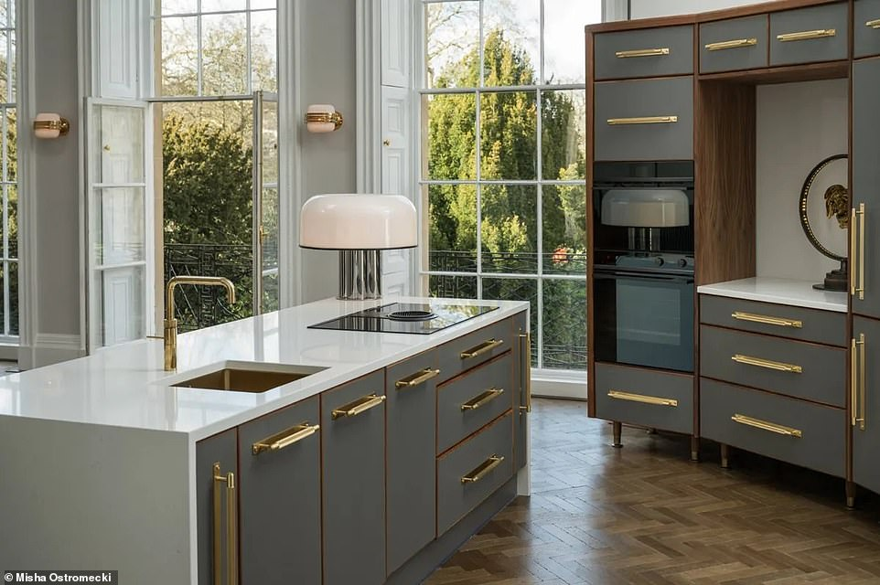 The newly installed designer kitchen has a pop-up extractor fan set in the centre of the hob on the kitchen island and brushed brass accessories