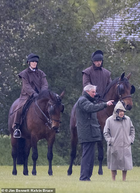 A member of the Queen's staff could be seen gesturing to the royal, as the pair studied Prince Philip's carriages and horses at Windsor Castle today