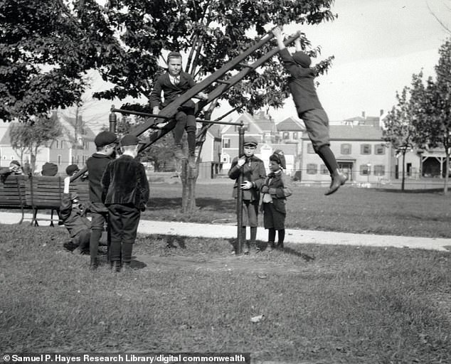 Students playing on an a large teeter totter, consisting of a ladder attached to a tall bar on the playground at the Kindergarten for the Blind in Jamaica Plain. The exact era is unknown