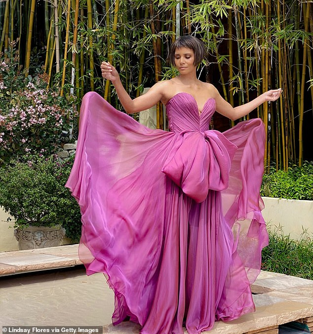 Gorgeous:Halle paired her choppy bob, which was longest in front where it framed her face, with a stunning sheer magenta gown with a voluminous skirt and a massive bow on her torso