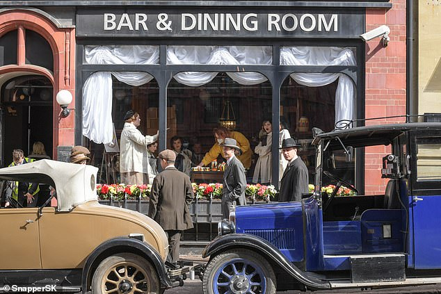 Ceramics: Old vehicles from the 1920s era were parked on the street in front of the large window where the girls sat