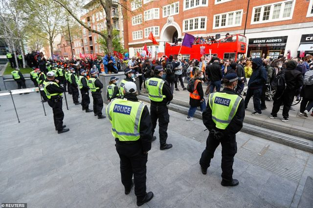 Police officers stand guard outside the Home Office on Saturday as hundreds of people arrive to demand the bill is killed