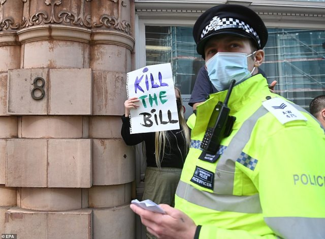 A police officer during the march in London today with a protestor seen holding up a 'Kill the Bill' sign in the background