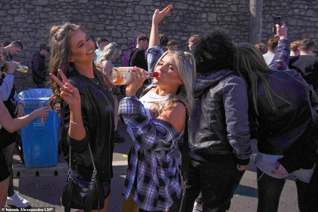 Revellers in Liverpool are seen drinking, smiling and taking photos together this evening as they wait to enter the Covid-19 pilot rave event being held at Circus night club at Bramley-Moore Dock