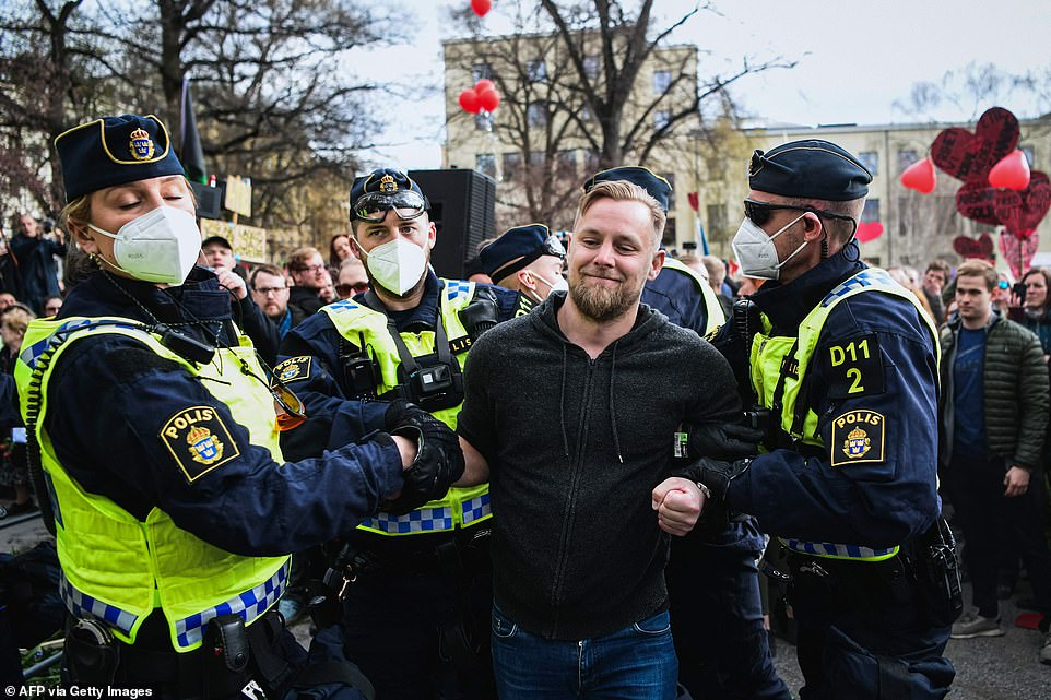 STOCKHOLM, SWEDEN: A man is led away from a group of demonstrators in the Swedish capital earlier today during May Day protests