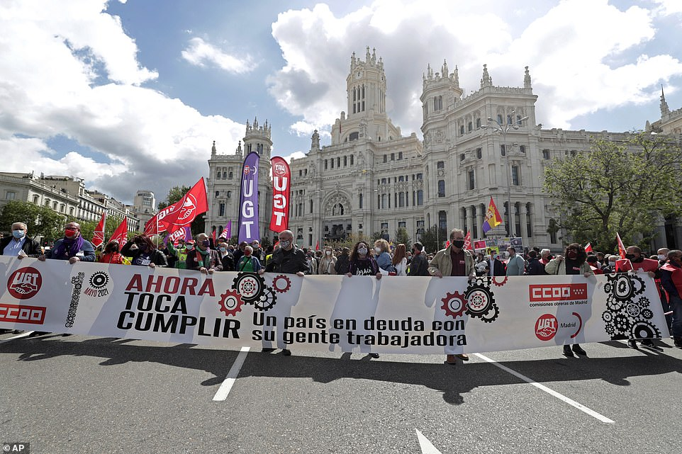MADRID, SPAIN:People march past the City Hall during the traditional May Day rally on Saturday