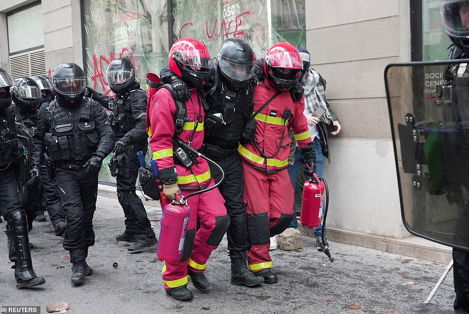 PARIS, FRANCE:Firefighters carry police officer away from clashes during the traditional May Day protests