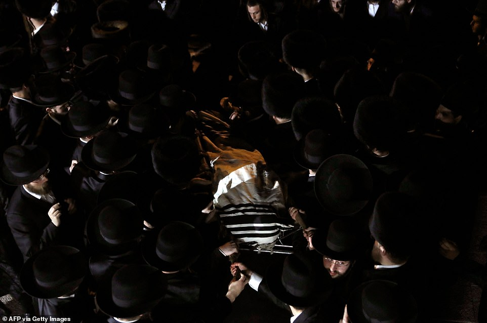 Ultra-Orthodox Jewish men take part in a funeral ceremony in Jerusalem for a victim of a stampede during a religious gathering in northern Israel