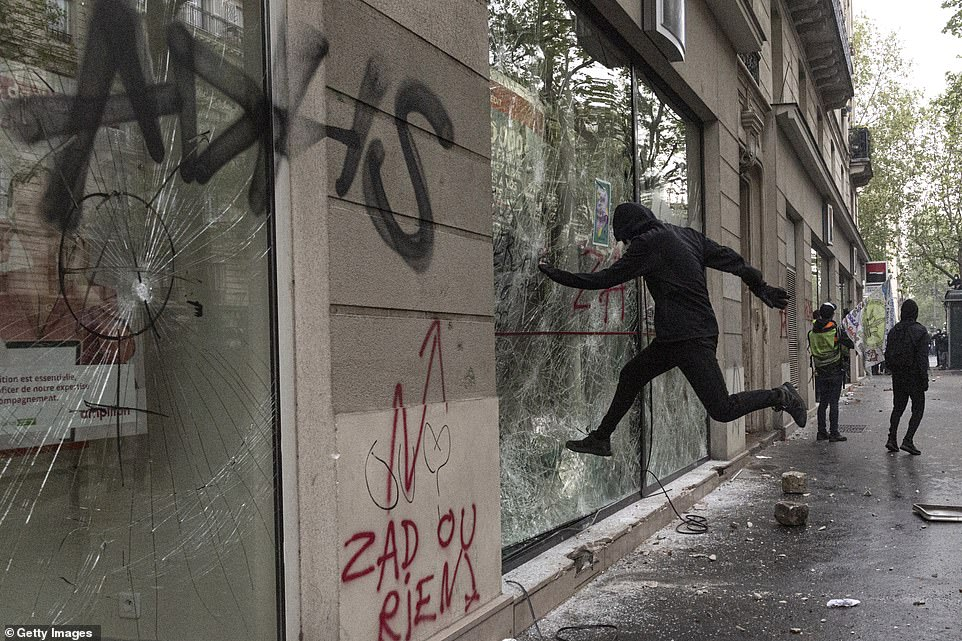 PARIS, FRANCE:A protester kicks in a bank window at the International Labour Day protests on May 1 as demonstrations turned ugly as the crowds vented their fury at Emmanuel Macron