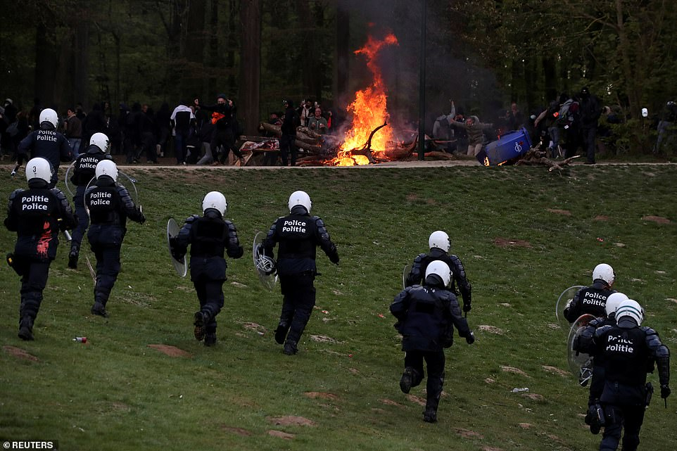 BRUSSELS, BELGIUM: Police officers in riot gear move up to an advanced position during clashes at a park in Brussels this evening