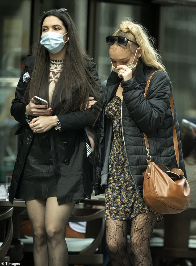 Friends: Roxy stepped out with a pal and linked arms as the pair sported face coverings while out and about