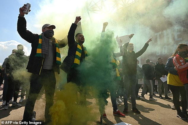 Fans in green and gold protest scarves chant outside Old Trafford on Sunday afternoon