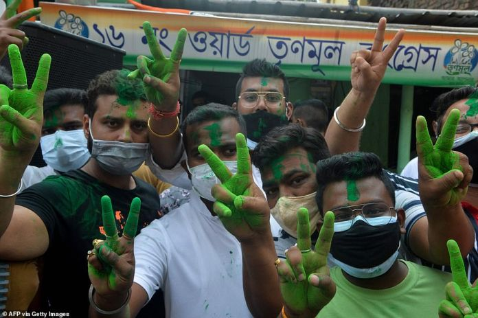 Congress party supporters flash the victory sign in Siliguri, West Bengal on Sunday after the incumbent chief minister's party defeated Modi's BJP