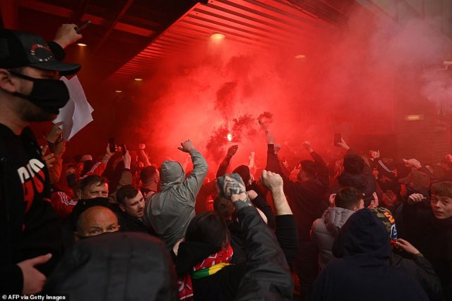 A red flare is let off inside Old Trafford as Manchester United fans protest on Sunday after they breached security lines