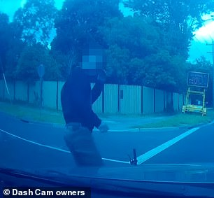 The cyclist (cyclist) appears shaken but not badly injured after a near-miss with a car
