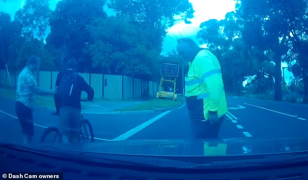 The driver ( in yellow) appears more concerned about any damage to his car than the cyclist