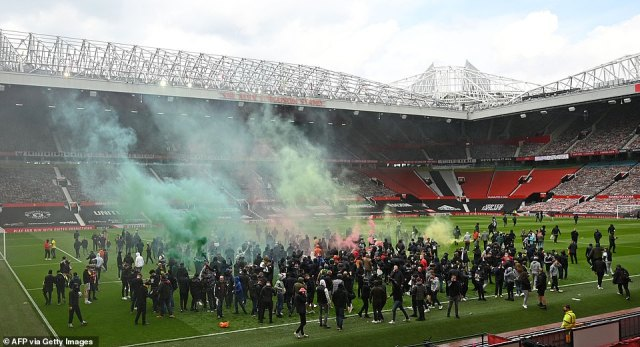 The crowd that breached Old Trafford perimeter gathered in front of the south stand, lighting smoke flares and chanting