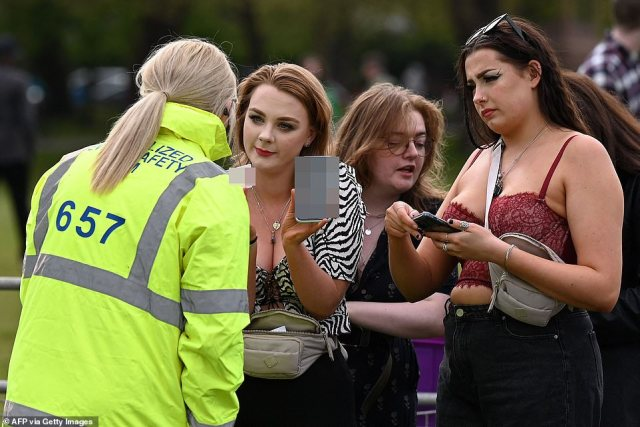 A concert-goers shows a negative Covid-19 result on their phone as well as their driving licence as they arrive