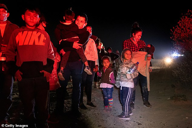 President Biden continued to blame the Trump administration for the situation at the border; above immigrant families wait to be processed by U.S. Border Patrol agents after crossing the Rio Grande into South Texas