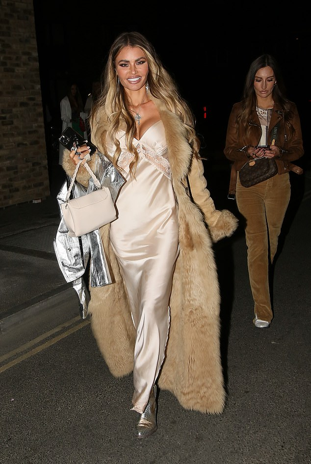 Glam:Sister Chloe made sure to command attention as she left the bar, as she wore a floor length champagne satin dress