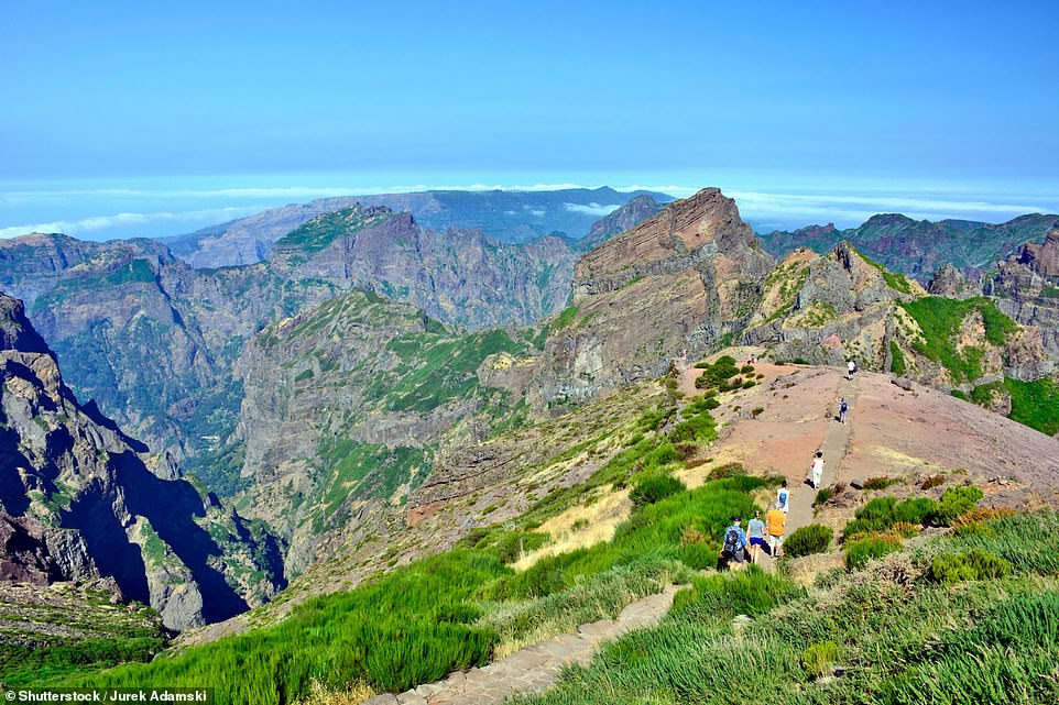 Visitors to Madeira can climb the jagged mountain staircase high above the cloud line to Pico do Arieiro, pictured, one of the island's tallest peaks