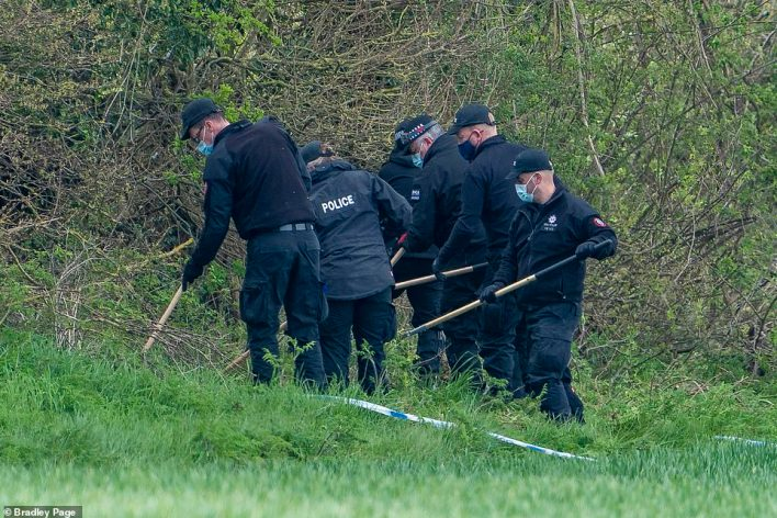 Police officers search bushes with poles close to the Ackhold Wood on Sunday