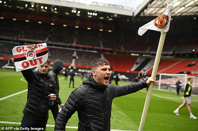 One fan among those who stormed Old Trafford grabbed the corner flag as they stormed pitch