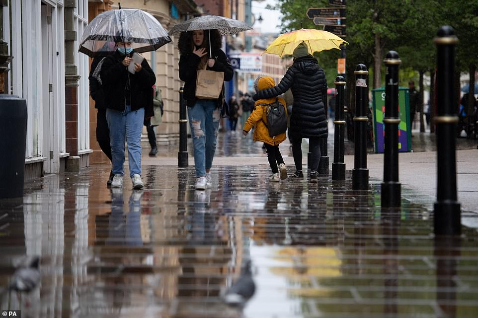 People holding umbrellas walk along High Street in Worcester as wet and windy weather covers much of the region