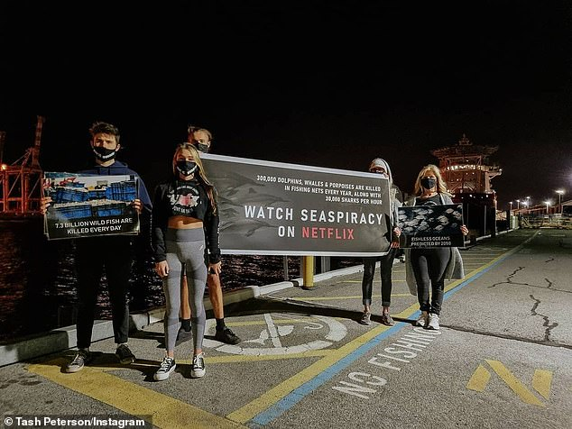 Outside the restaurant, a group held a banner (pictured) that encouraged patrons to watch the Netflix documentary Seaspiracy
