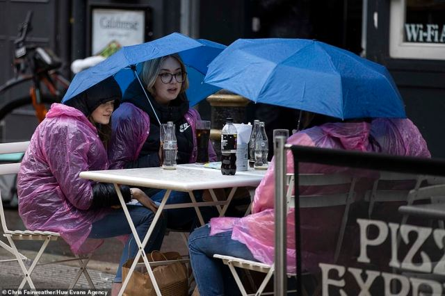 Diners were seen in rain ponchos huddled under umbrellas as they sat outside in Cardiff city centre