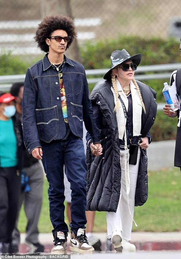 Young love: The two held hands on the sidelines of the youth sporting event in Los Angeles on Sunday