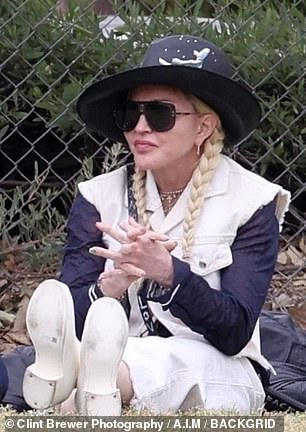 Cute: Madonna could be seen cheering for her son on the sidelines of the pitch
