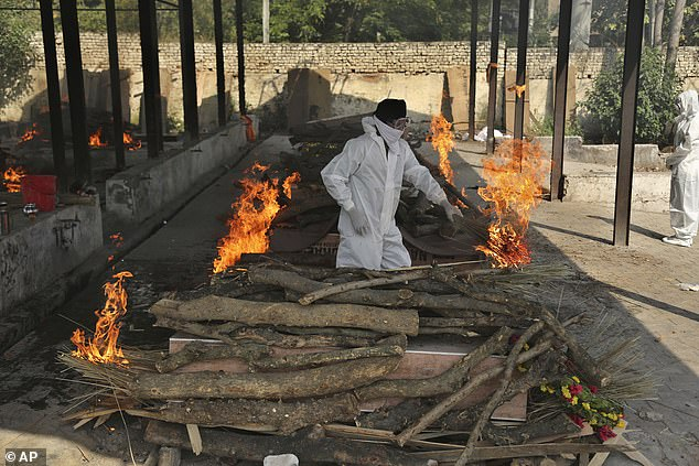 A family member performs the last rites of a COVID-19 victim at a crematorium in Jammu
