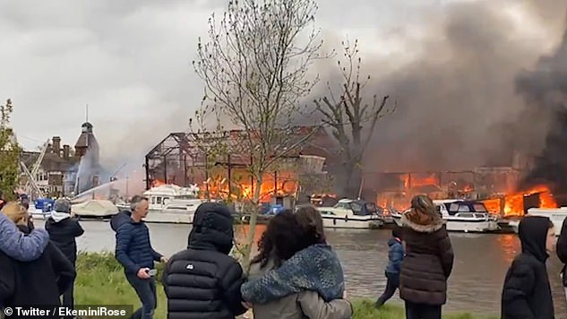 Onlookers view the terrifying blaze on Platt's Eyot in Hampton, which destroyed two buildings