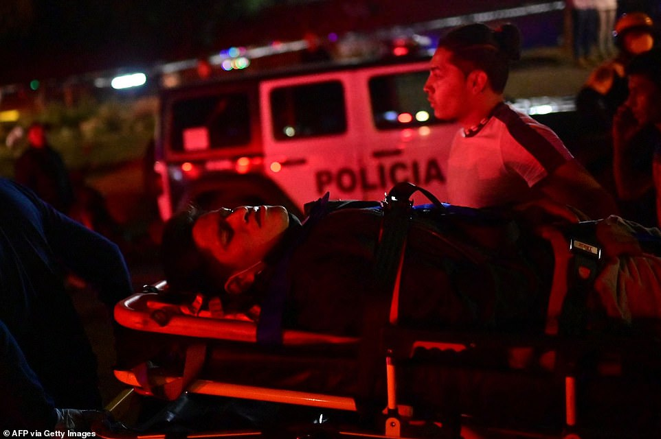 Emergency workers carry an injured person away on a stretcher after a train overpass partially collapsed in Mexico City
