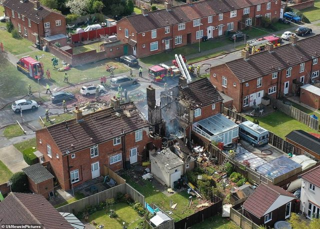 Neighbours described how the explosion in Ashford 'shook' the whole street at just before 8am, with seven fire engines racing to the scene. Pictured: An aerial photo of the destroyed house, with only the chimney remaining standing