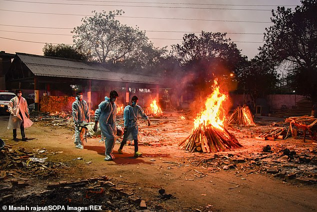 Workers carry the body of a person who has died of the Covid-19 coronavirus disease as other funeral pyres are seen burning during a mass cremation held at a crematorium on May 3 2021