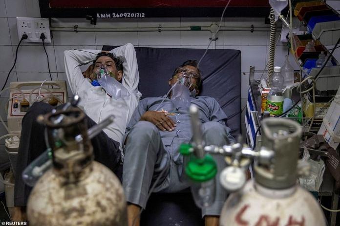 Los pacientes de Covid que comparten una cama en el hospital frente al campo de cricket reciben oxígeno mientras luchan por sus vidas.