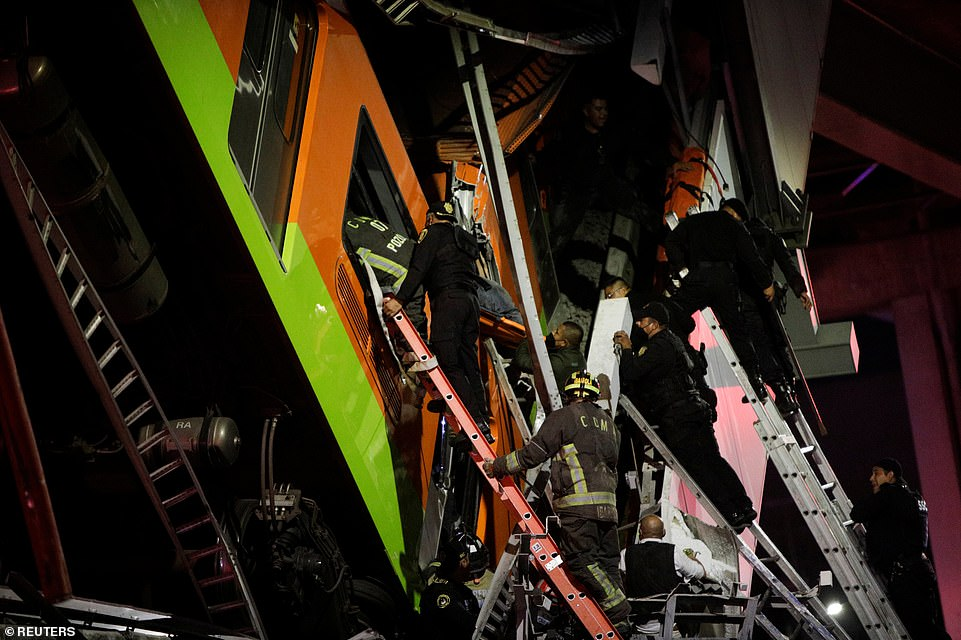 Rescuers erect ladders to make their way inside the train carriages, before being temporarily called off amid warnings it is unstable and their movements could cause another collapse