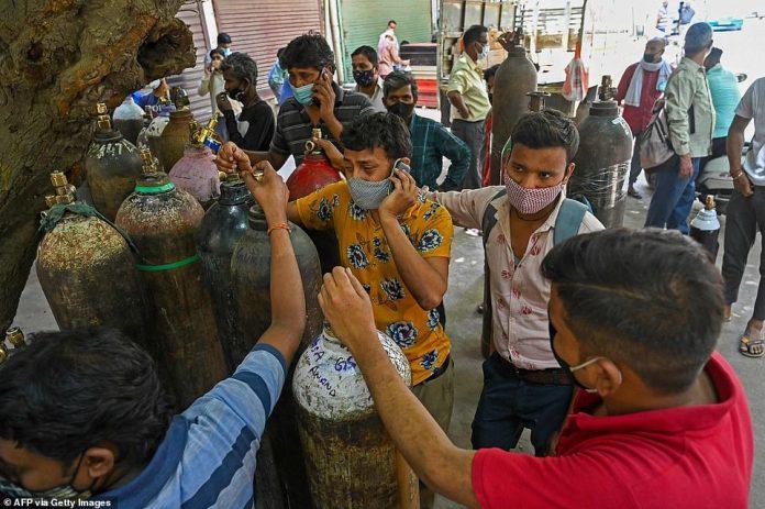 Familiares desesperados de pacientes con coronavirus esperan para rellenar cilindros.  Los cilindros de oxígeno completos cuestan alrededor de £ 1,000