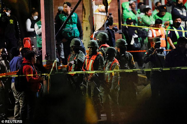 Paramilitary workers holding rifles are seen near the scene of the collapse, as a cordon was set up to keep people away