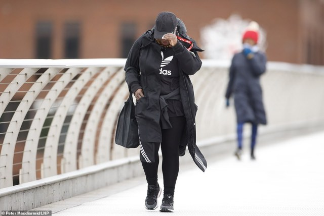 Parts of the UK were battered by 60mph winds overnight as gusts swept in from the north west and along England's south coast and temperatures plummeted to 1C in some places. Pictured: A pedestrians braves the gusts in London today