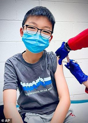 In an earnings call on Tuesday, Pfizer said it plans on asking the FDA for full approval this month and to ask for approval for kids ages 2 to 11 in September. Pictured:Caleb Chung receives the first dose of either the vaccine or placebo in a trial, December 2020