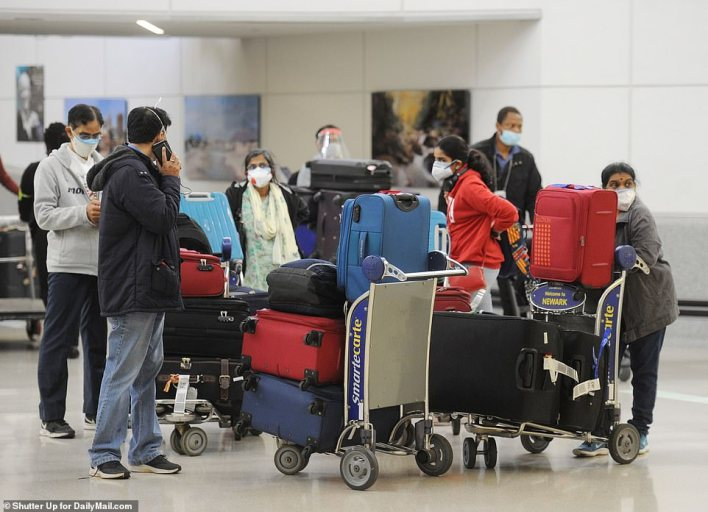 A family waits for their luggage in the Newark baggage claim after flying in on an Air India flight from Delhi or Mumbai. Both direct routes will still operating on Tuesday