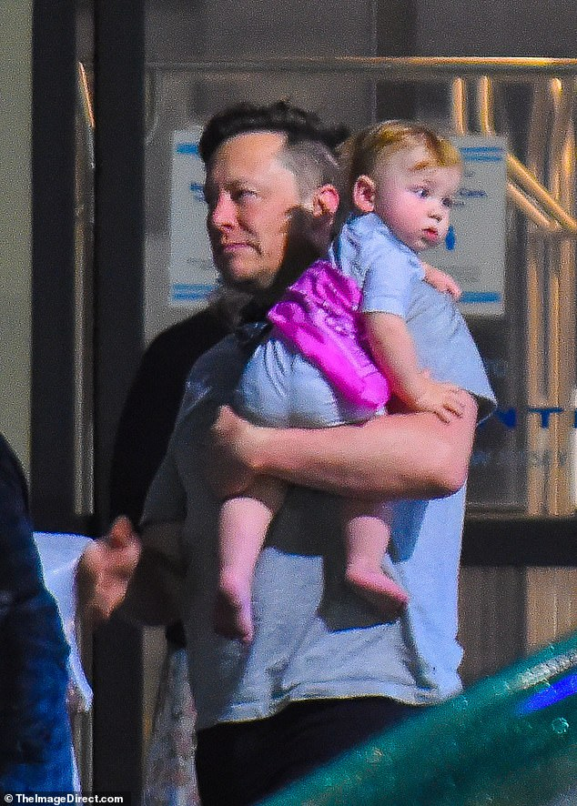 Doting dad: After landing at New Jersey's Teterboro Airport, the 49-year-old Tesla CEO carried their son X Æ A-XII, who turns one this month