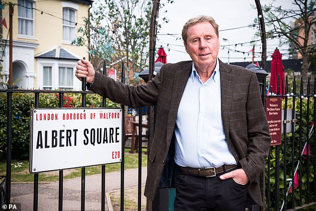 Landmark: The 74-year-old former footballer poses next to the show's famous Albert Square sign in official photos of him on set were released on Tuesday